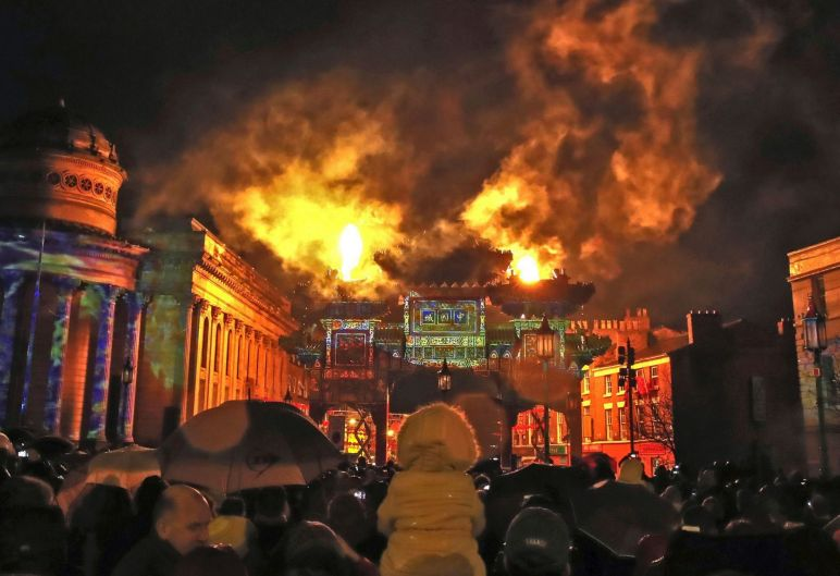 People watch the pyrotechnics and a light-show as Liverpool's Chinese Arch is lit up as the city holds its annual ...
