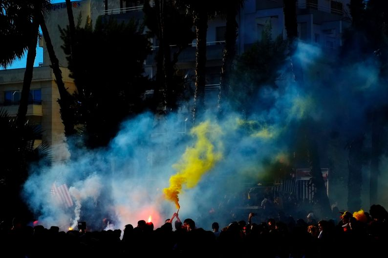 People in carnival clothing hold up flares during the Carnival parade celebrations in Cyprus' coastal city of Limasso.