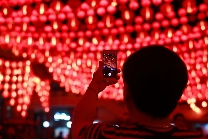A Malaysian ethnic Chinese man takes a souvenir photograph of illuminated traditional Chinese lanterns on the third day ...