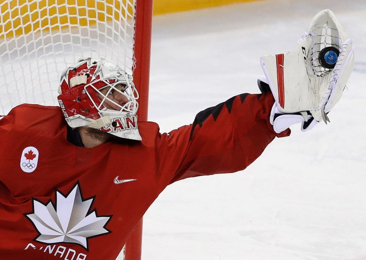 goalie Kevin Poulin (31), of Canada, grabs the puck during the third period of the preliminary round of the men's hockey ...