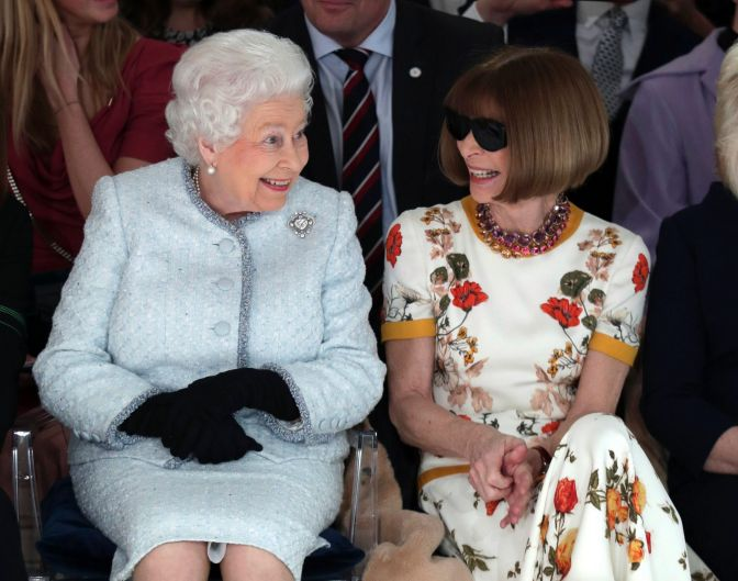 The Queen of Fashion meets the Queen of England. Britain's Queen Elizabeth sits next to fashion editor Anna Wintour as ...