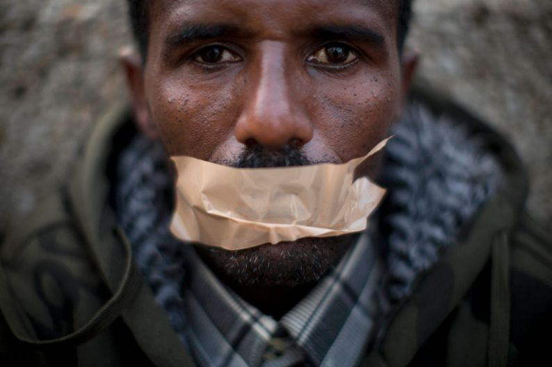 AnAfrican migrant covers his mouth with tape during a protest in front of the U.S. embassy, demanding asylum and work ...