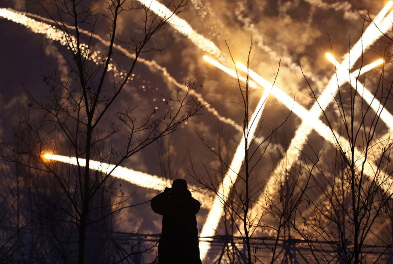 A man watches fireworks from an Olympic celebration at the 2018 Winter Olympics in Pyeongchang, South Korea.