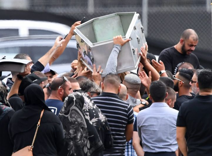Mourners lift an empty coffin above their heads during the burial of Mahmoud 'Mick' Hawi at Rookwood Cemetery in Sydney.
