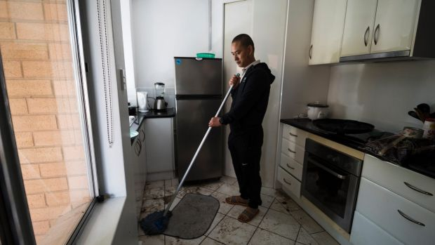 Sangay Yeser cleaning his apartment after flooding in O'Connor.