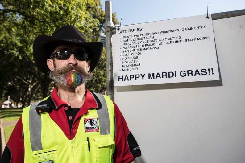 A security guard with a rainbow beard checks credentials at the marshalling area.