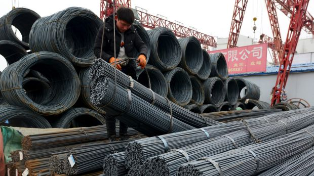 A worker loads steel products onto a vehicle at a steel market in Fuyang in central China's Anhui province.