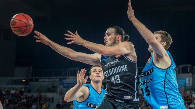 Quick hands: Melbourne captain Chris Goulding dishes off a pass from under the basket in the first semi-final against ...
