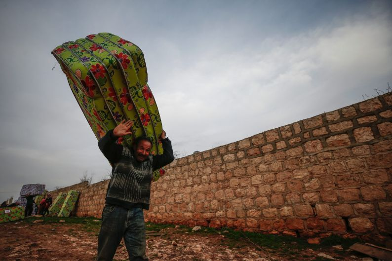 A man carries mattresses received as humanitarian aid distributed by the Red Crescent, in Mersewa village, in the ...