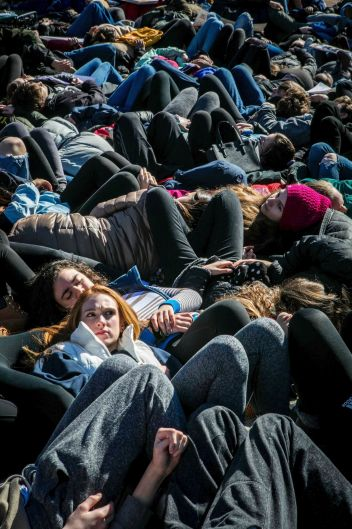 "Pioneer High School senior Mia Steinhauer lies down on the ground during the ""die-in"" Saturday, Ann Arbor, Michigan."