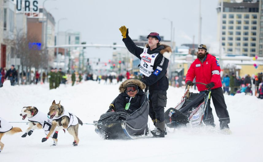 Iditarod musher Allen Moore waves to the crowd during the ceremonial start of the Iditarod Trail Sled Dog Race in ...