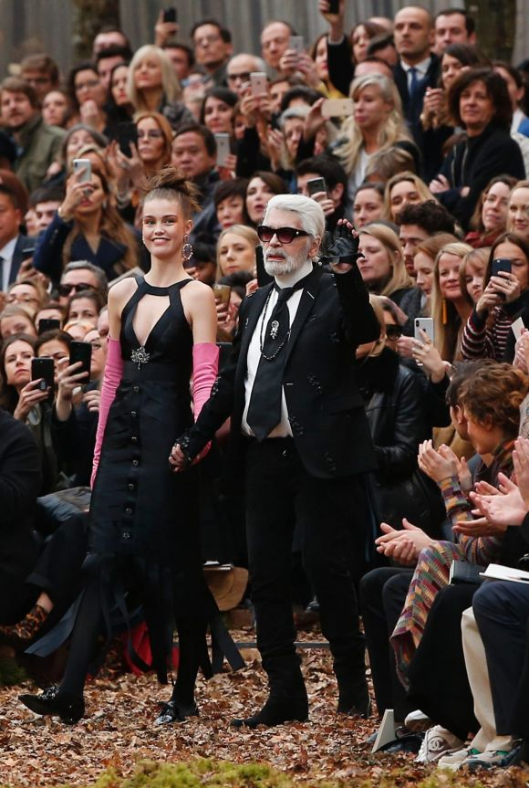 Designer Karl Lagerfeld, poses with a model during the Chanel ready-to-wear fall/winter 2018/2019 fashion collection.