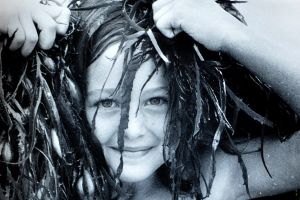 Fiona Game, 7, of Deakin plays with seaweed at Broulee Beach. (1986).