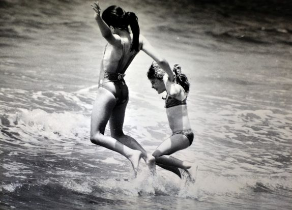 Gowrie girls Robyn Lette, 11, and Kiera Van Kleef, 5, grin and bear it as they jump waves at Casey Beach Batehaven. (1993).
