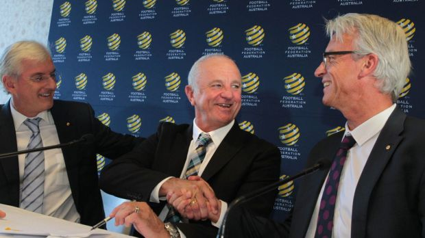 Graham Arnold shakes hands with FFA CEO David Gallop as FFA Chairman Steven Lowy looks on during a press conference to ...
