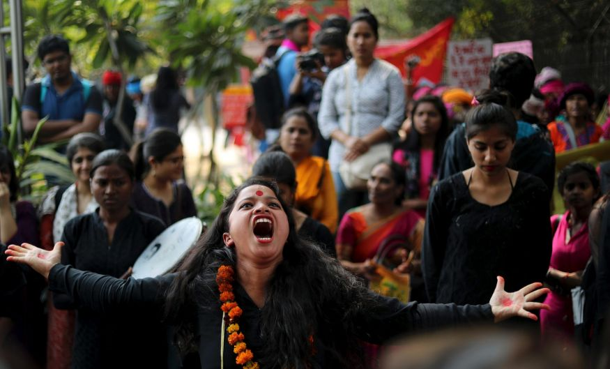 An Indian woman performs a street play highlighting domestic violence before the start of a march on International ...