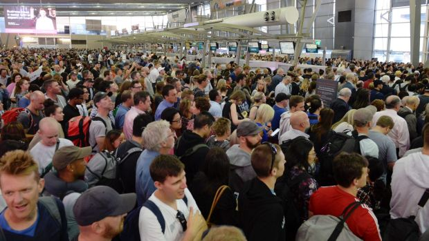 Passengers at thedomestic terminal wait to go through security after technical issues effectively shut down the airport ...