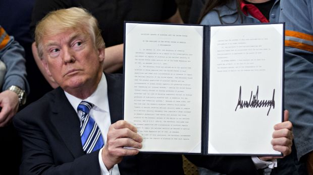 Donald Trump holds a signed proclamation on adjusting imports of aluminium into the United States in the Roosevelt Room ...