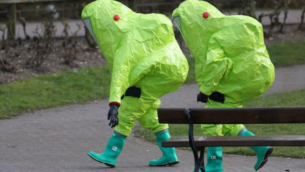 Personnel in hazmat suits walk away after securing the covering on a bench in the Maltings shopping centre where former ...