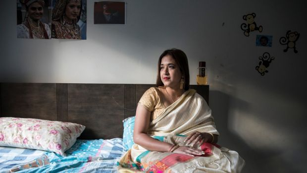 Himali Nayak sits on her bed in her Westmead apartment.