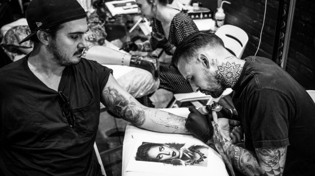 Elric Gordon focuses on a tattoo on a client at the Australian Tattoo Expo.