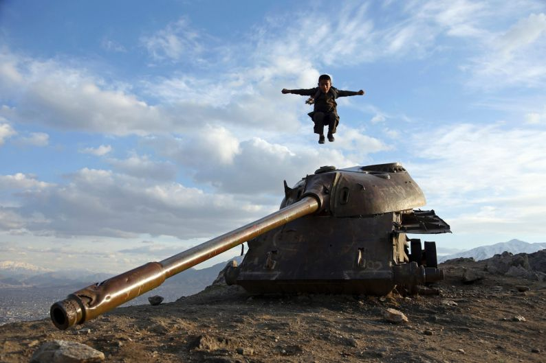 An Afghan boy jumps off the turret of a Soviet tank on a hilltop on the the outskirts of Kabul.