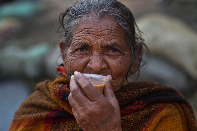 Gujeria, 81, drinks tea while waiting for customers at her street side fish stall in Gauhati, India. In India, hundreds ...