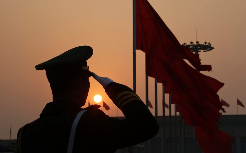 A Chinese paramilitary policeman salutes as delegates leave the Tiananmen Square after attending a plenary session of ...