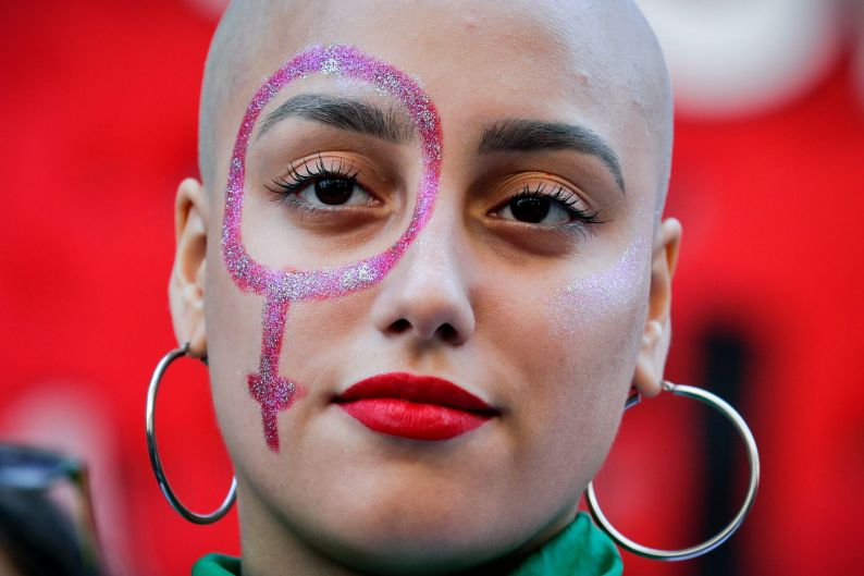 A pro-abortion activist with a Venus symbol painted on her face listens to a speech outside of Congress after the ...