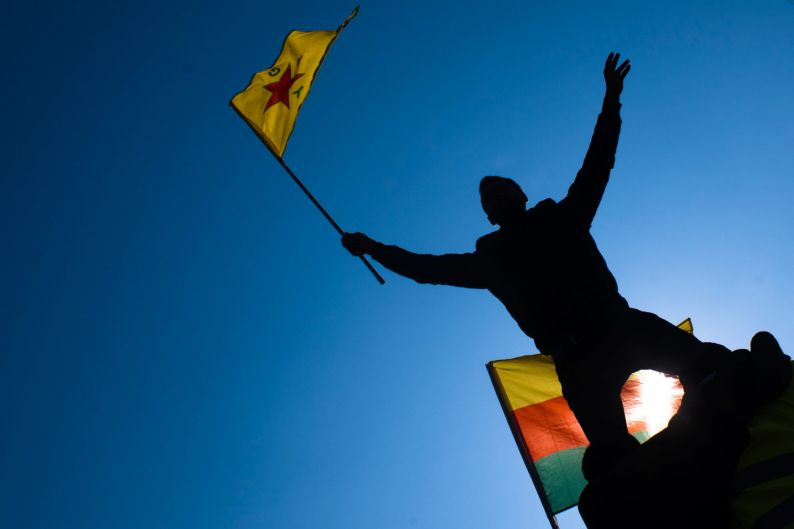 A man waves a flag with Kurdish symbols as he attends a demonstration of some thousand protestors against the Turkish ...