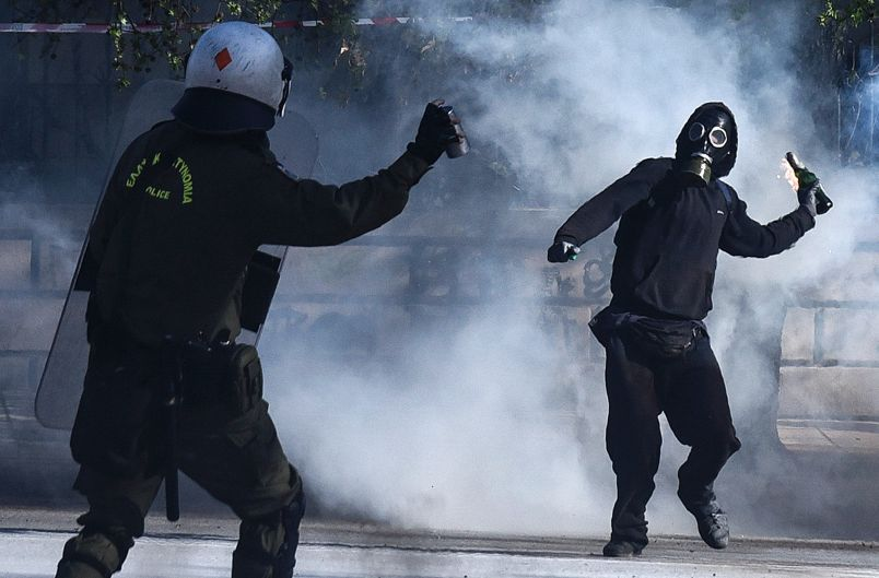 A masked protester throws a molotov cocktail at riot policemen during clashes outside the University of Thessaloniki ...