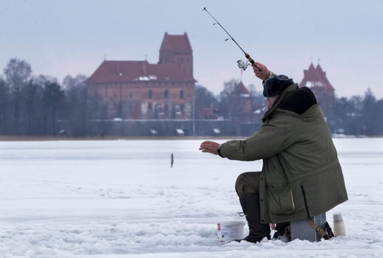 A local fisherman fishes on a frozen, snow-covered Galve lake as temperatures are just 2 degrees Celsius in Trakai, some ...