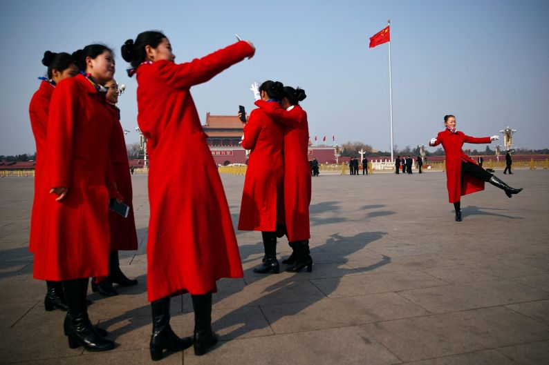 Hospitality staff members take souvenir pictures on Tiananmen Square during a plenary session of Chinese People's ...
