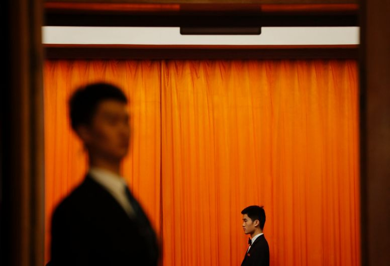 Chinese security personnel in usher uniforms stand guard during a plenary session of Chinese People's Political ...