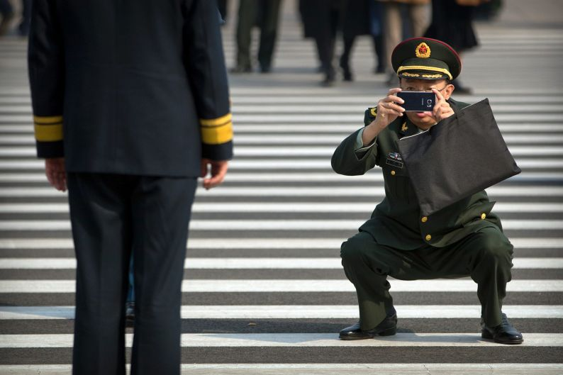 A military officer takes a smartphone photo of a fellow officer before a plenary session of the Chinese People's ...