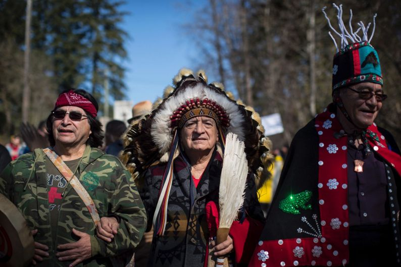 Hereditary Chief Phil Lane Jr., center, joins other indigenous chiefs and elders in leading thousands of people in a ...