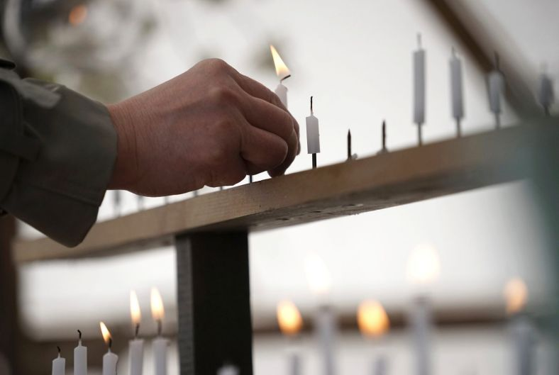 A man lights a candle to mourn for victims of the March 11, 2011 earthquake and tsunami prior to a special memorial ...