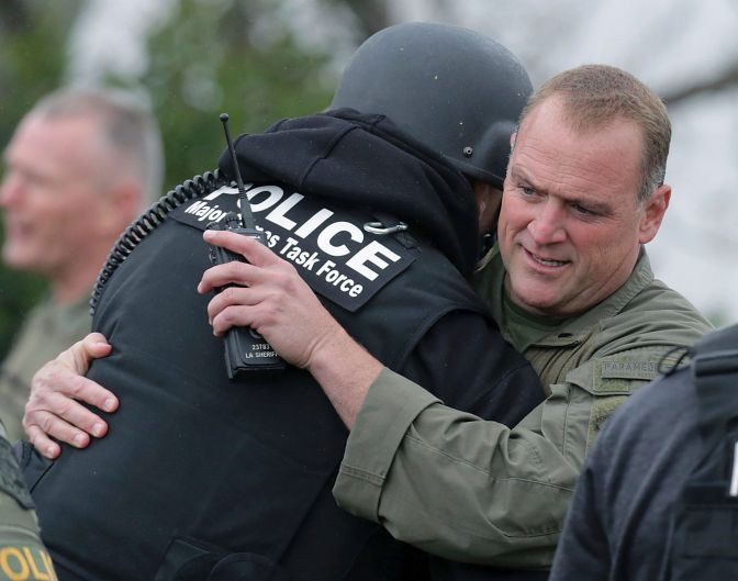 Pomona Police officers hug after a 15 hour stand-of. A gunman who shot two California police officers, killing one of ...