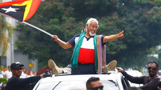 East Timorese independence hero Xanana Gusmao waves a national flag upon arrival in Dili on Sunday.