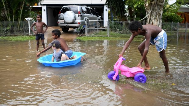 Children play in flood waters in Ingham on Sunday.