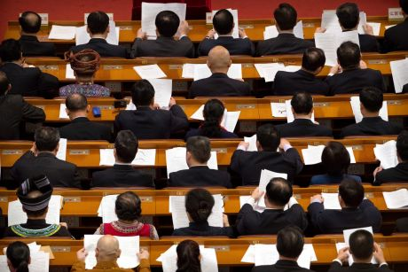 Delegates read paperwork before a plenary session of China's National People's Congress in Beijing.