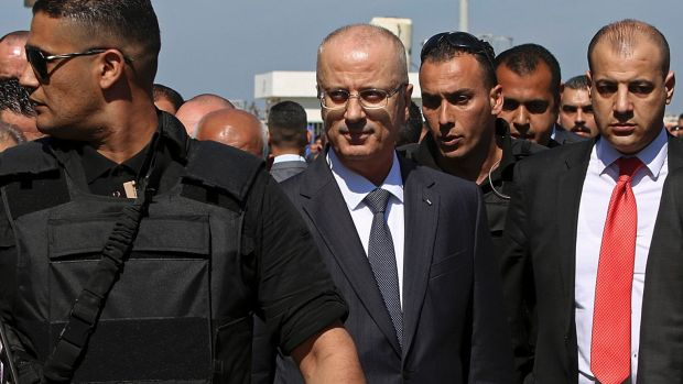 PM Rami Hamdallah (center), surrounded by bodyguards, arrives for the opening of a sewage plant project.