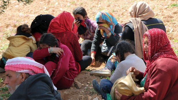 Syrians fleeing fighting between Turkish troops and Syrian Kurdish militia rest in a field between Afrin and Azaz, ...
