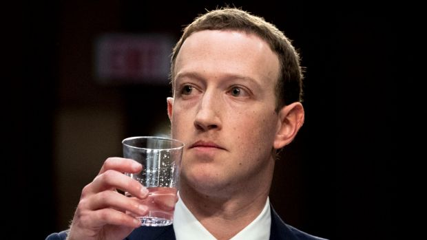 Facebook CEO Mark Zuckerberg takes a drink of water while testifying before a joint hearing of the Commerce and ...
