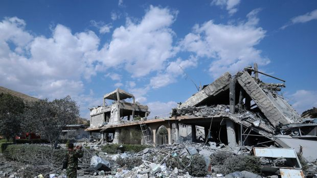A Syrian soldier films the damage of the Syrian Scientific Research Center.