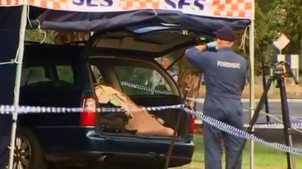 Forensic police examine boot of car.