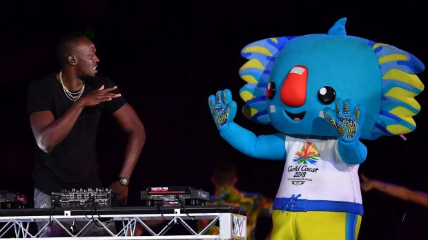 Usain Bolt performs on stage with the Games mascot, Borobi, during the closing ceremony.