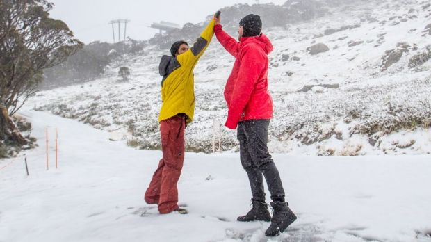 Thredbo visitors celebrate 5cm of fresh snow with a high-five.