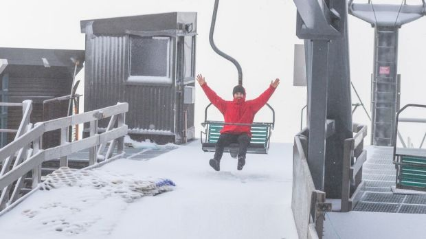 A Thredbo visitor gets ready to ride the chairlift after 5cm of fresh snow fell at the weekend.