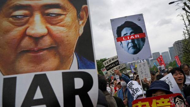 "Demonstrators hold up signs reading ""Liar"" during a protest against Japan's Prime Minister Shinzo Abe outside the ..."